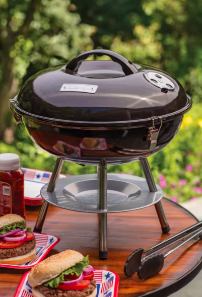 A black portable charcoal grill on a tabletop with dressed up burgers