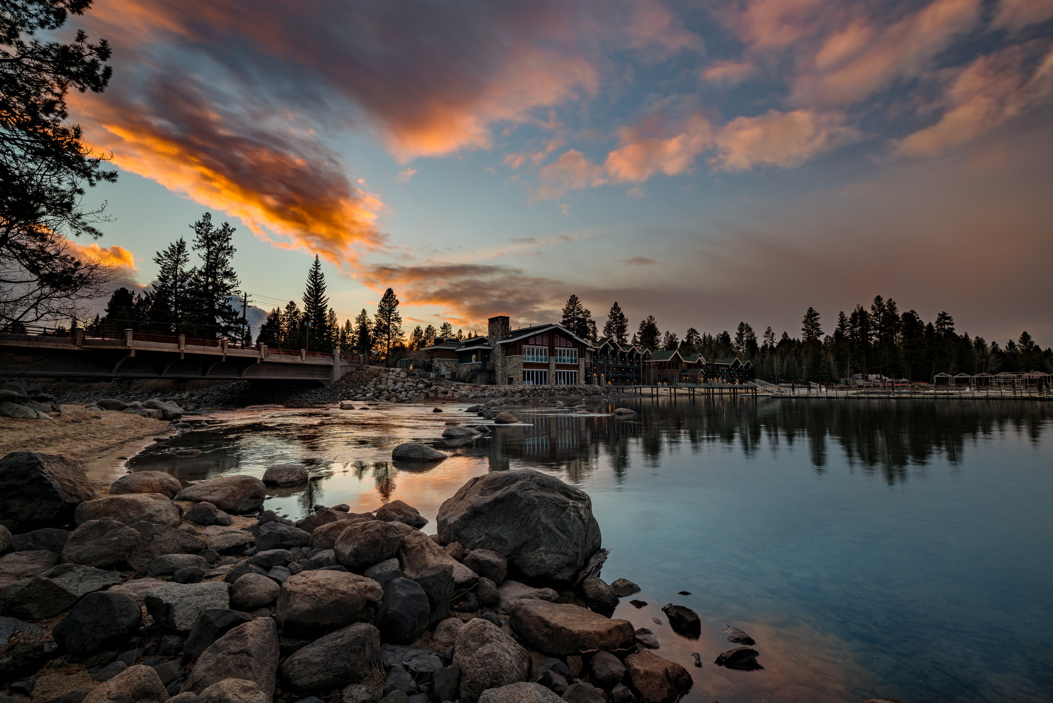Sunset on Payette Lake with hotel and cloud reflections in the water shoreline