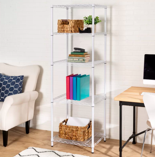 White shelving unit holding colorful binders, a wicker basket, and plants in a room