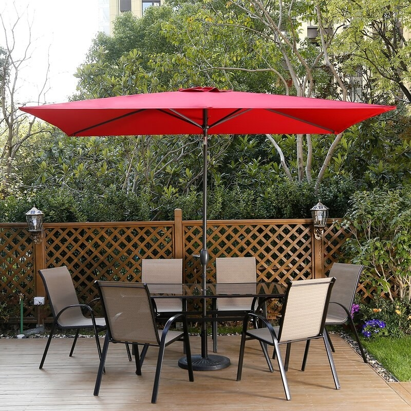 An umbrella sticking out of a table and providing shade for the table and six chairs