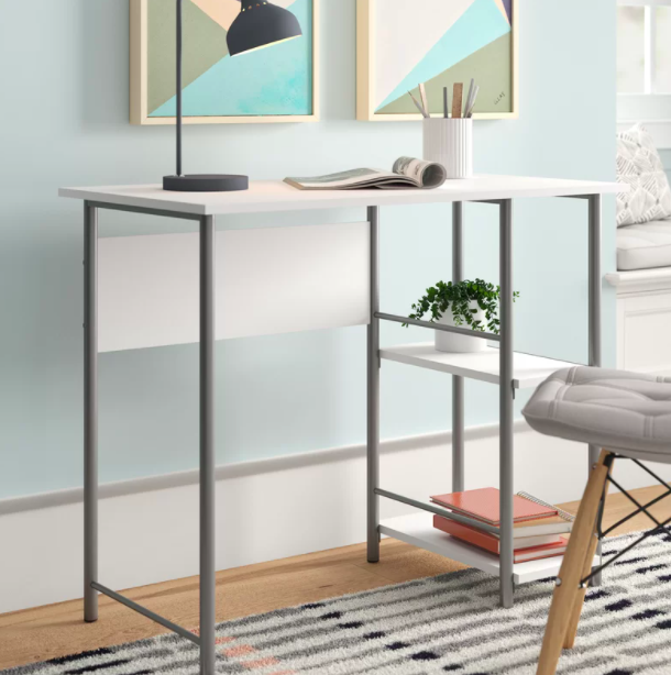 A white and silver desk with a cable management feature against a blue wall