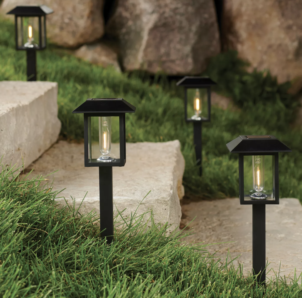 A set of pathway lights sticking out of the grass on both sides of a set of a stairs