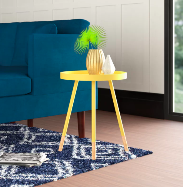 A small yellow accent table with a vase next to a dark blue sofa