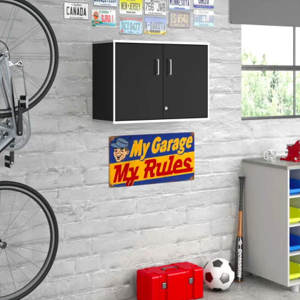 A black wall storage cabinet hanging up in a garage next to sports equipment