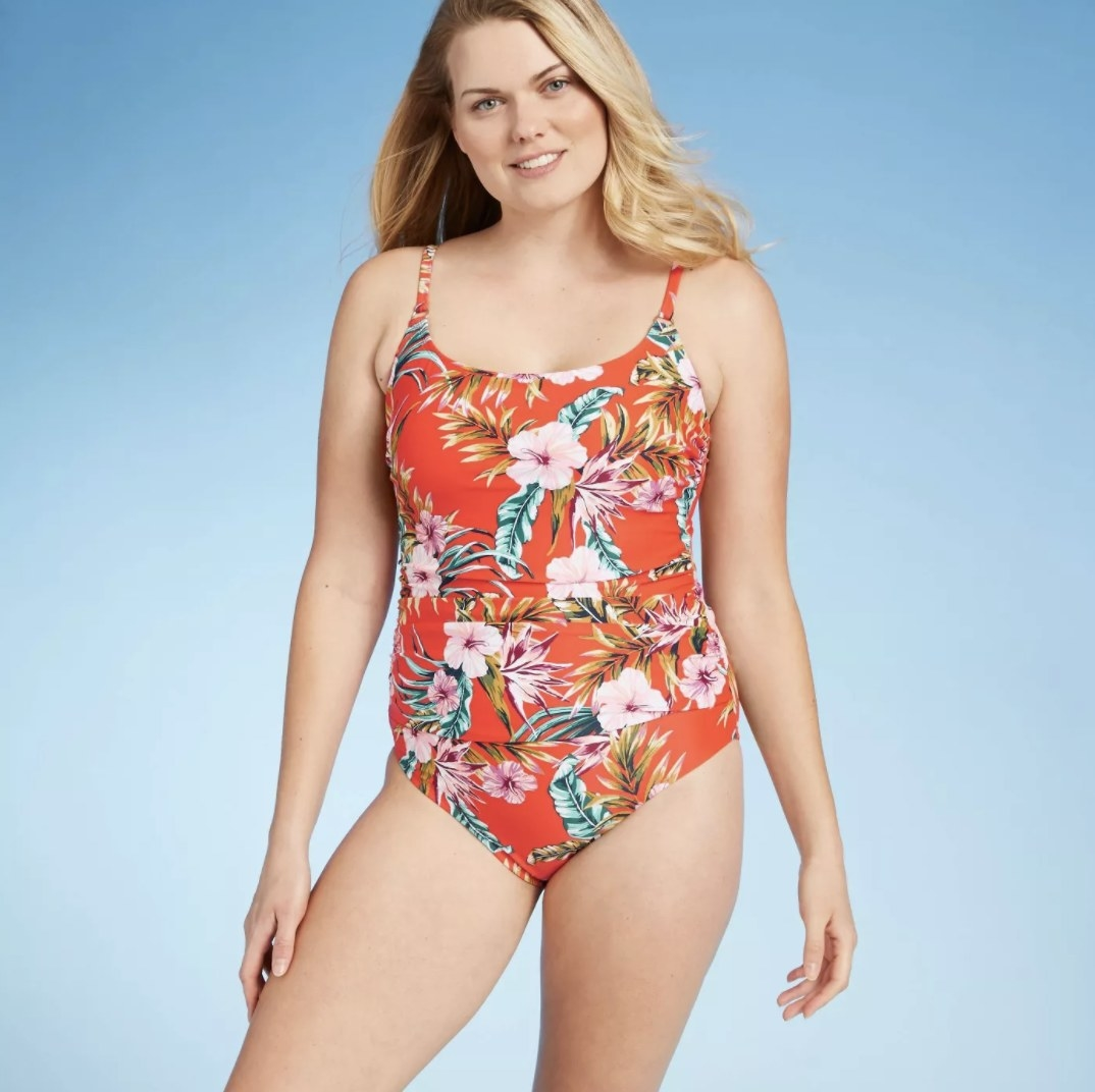 A model in an orange strapped one-piece with floral designs on it