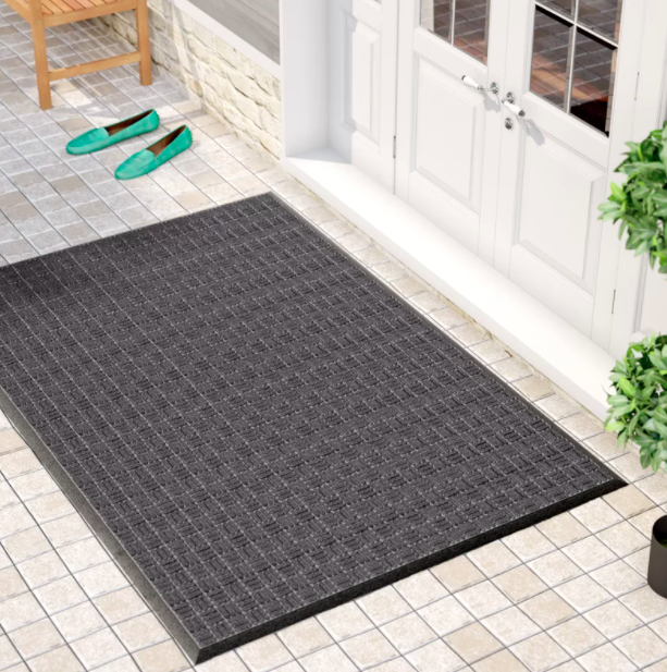 A black and gray non-slip indoor door mat on a tiled white floor