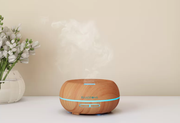 A wood tabletop humidifier next to a clear vase of flowers