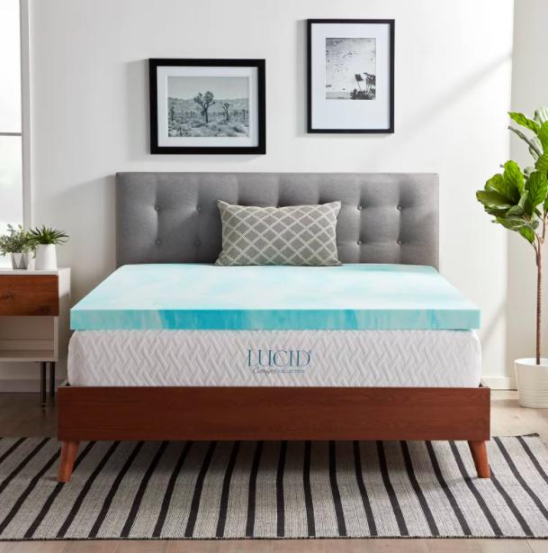 A gel swirl memory foam mattress topper on top of a wood bed frame