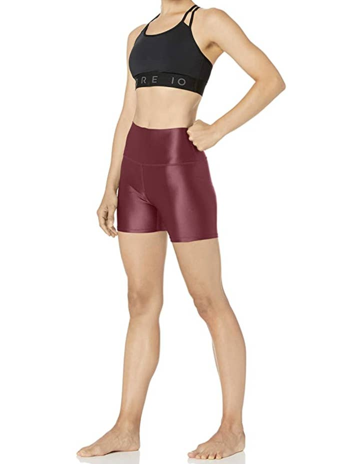 A model in deep red metallic bike shorts that fall mid-thigh