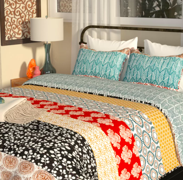 A reversible patterned quilt draped over a bed with blue accent pillows