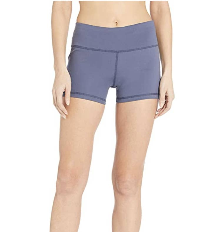A model in pastel blue bike shorts that fall on the upper thigh