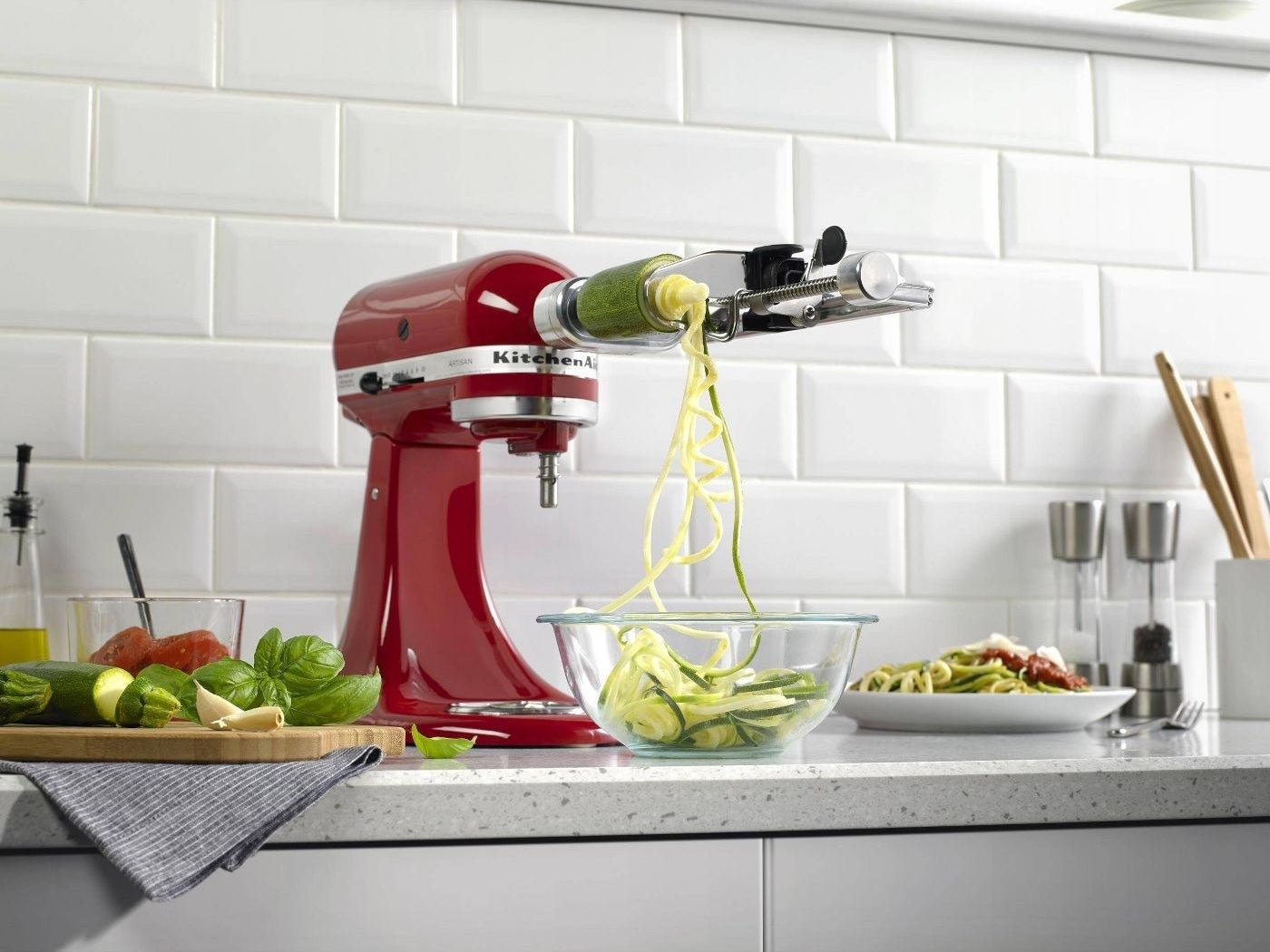 a red kitchen aid mixer with the stainless steel attachment making zucchini noodles