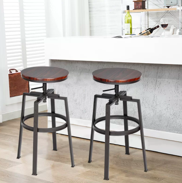 Two brown and black adjustable bar stools next to a white bar
