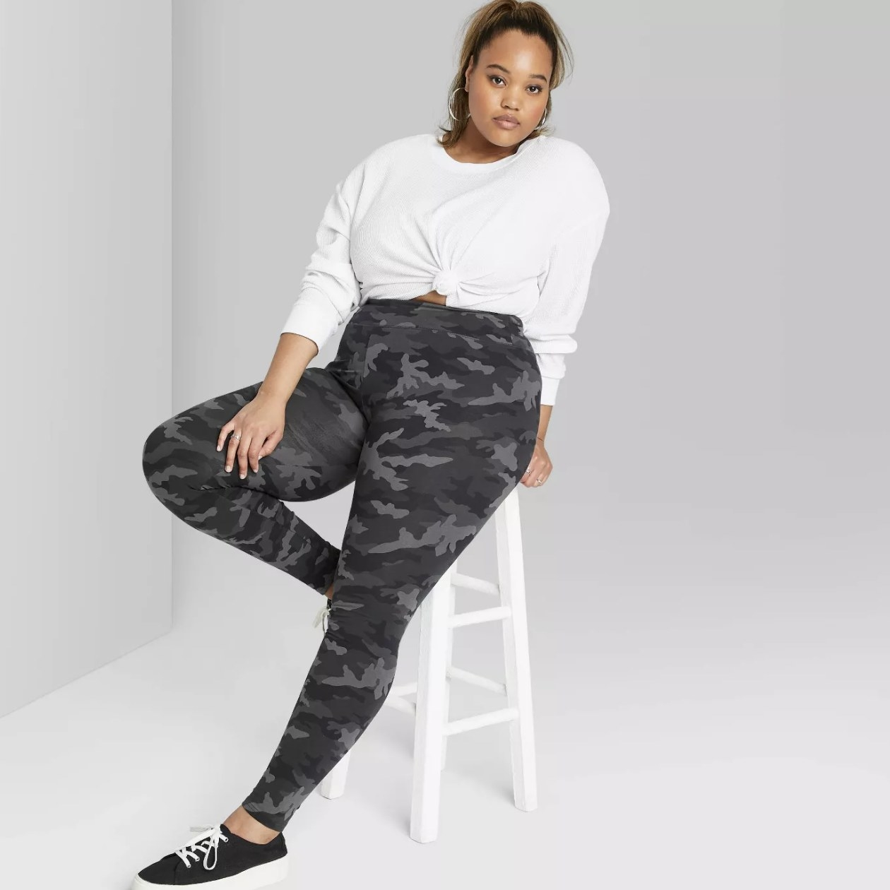 Model wearing the gray camo leggings with a white shirt