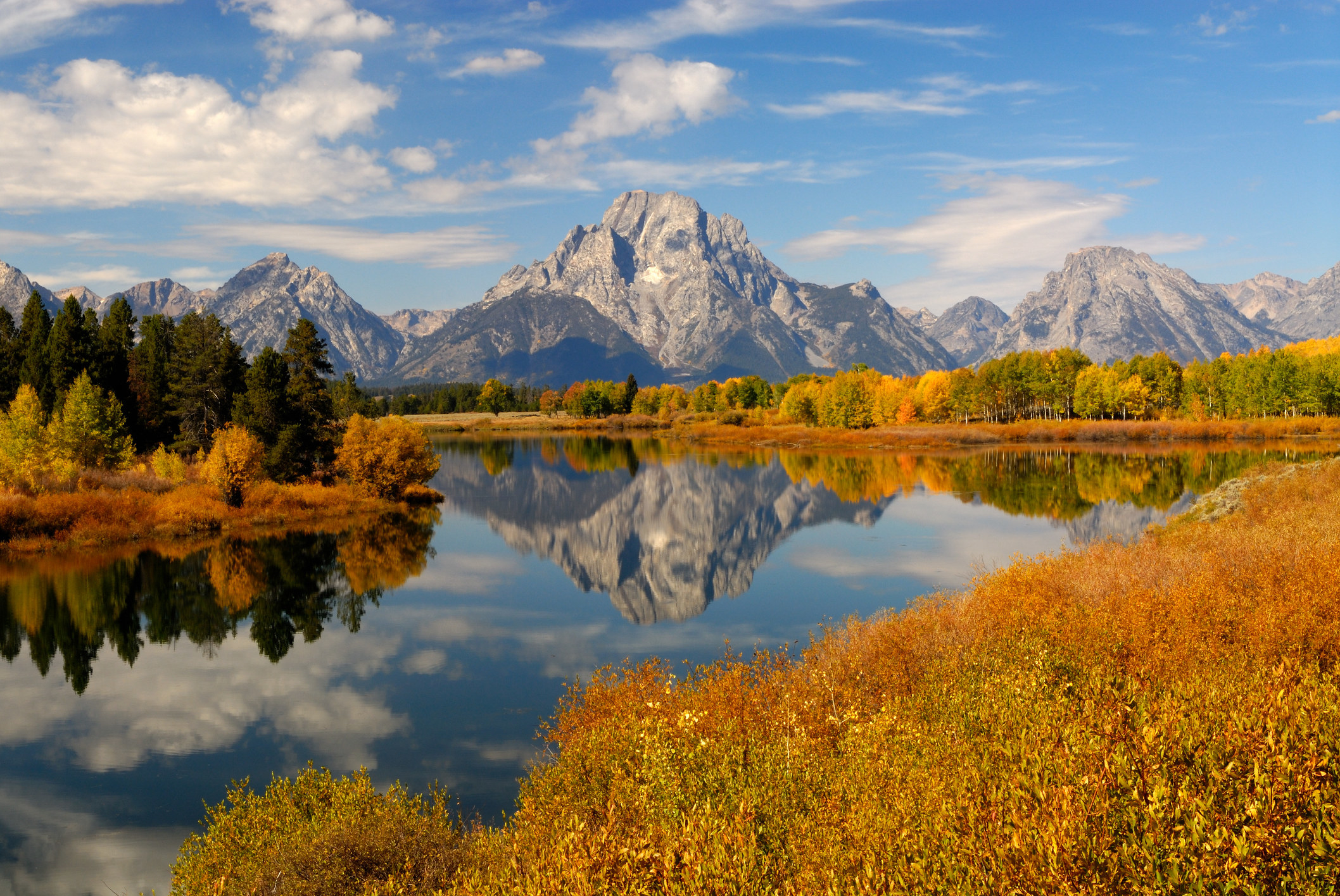 View of Mount Moran reflected in a river with fall foliage on the shores