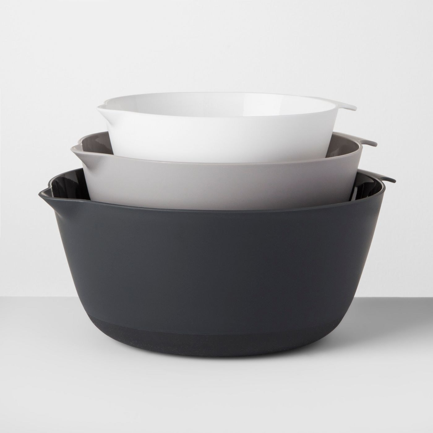 a set of three mixing bowls that fit inside one another and are white, grey, and black