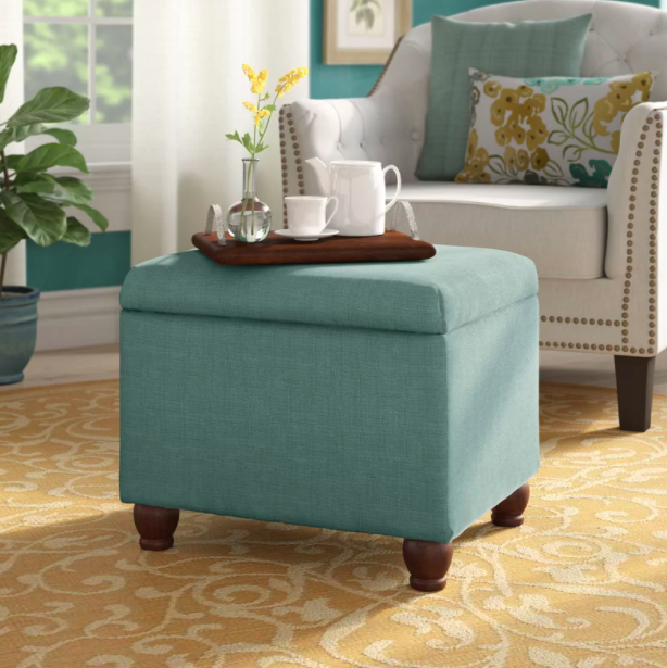 A green storage ottoman with a tea set and vase on top