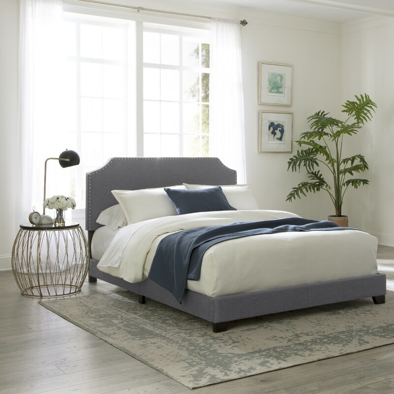 The bed frame in stone gray, featuring a nailhead trim