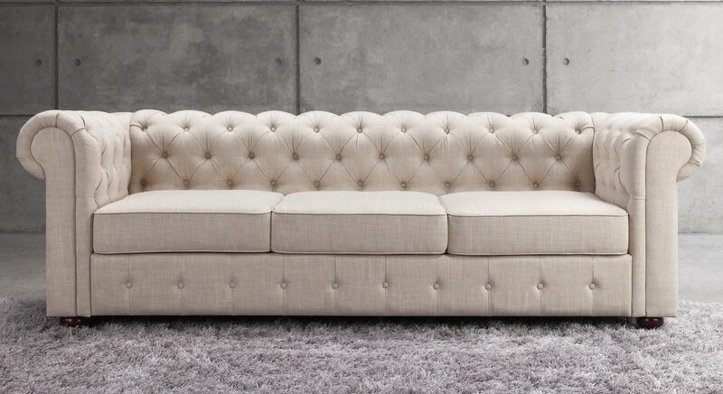 The sofa in ivory, featuring a tufted back