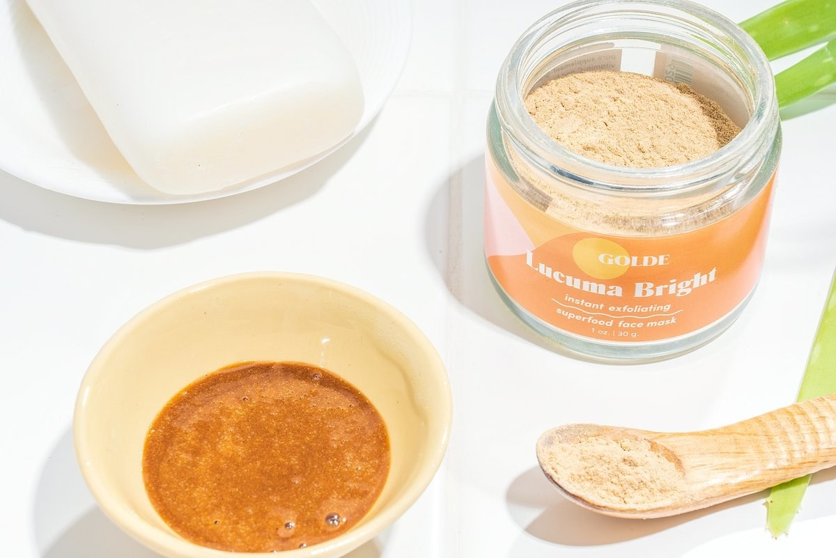 The golden-colored mask as a powder before mixing next to the mask mixed with water
