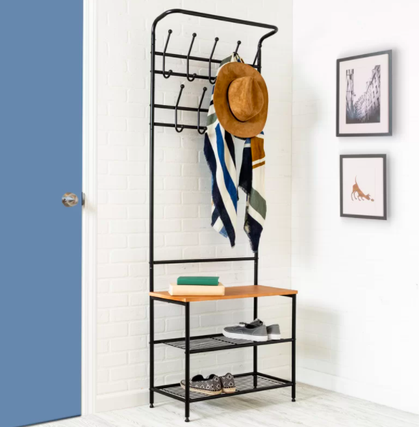 A black entryway storage unit displaying a wide-brimmed hat, a colorful scarf, and shoes