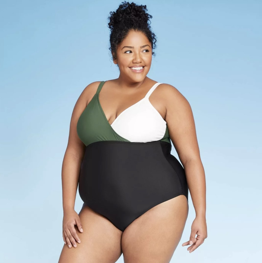 A model in a one piece that is black on bottom, green on the right side of the chest, and white on the other