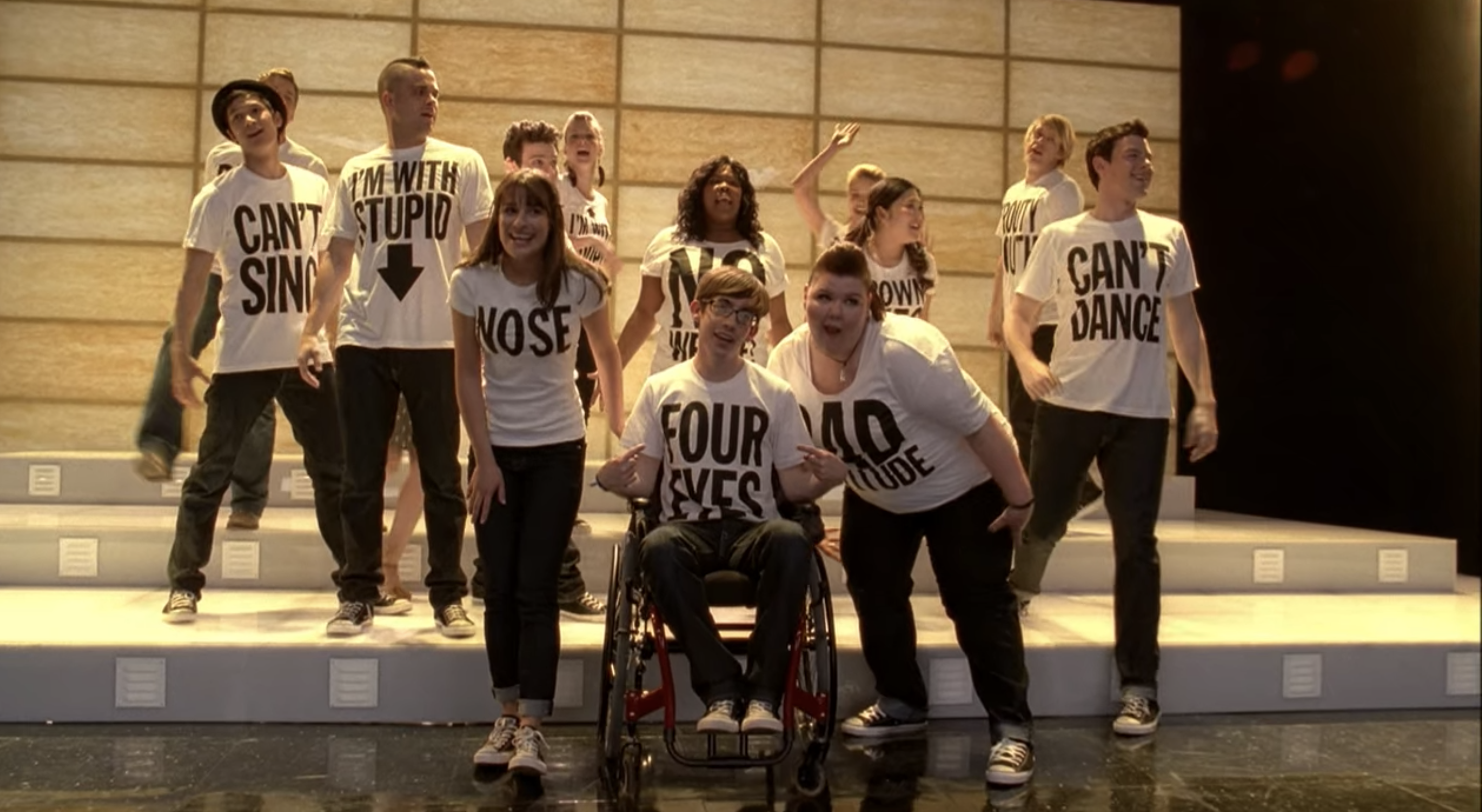The New Directions sing on stage while wearing white T-shirts that state the individual traits they are proud of.