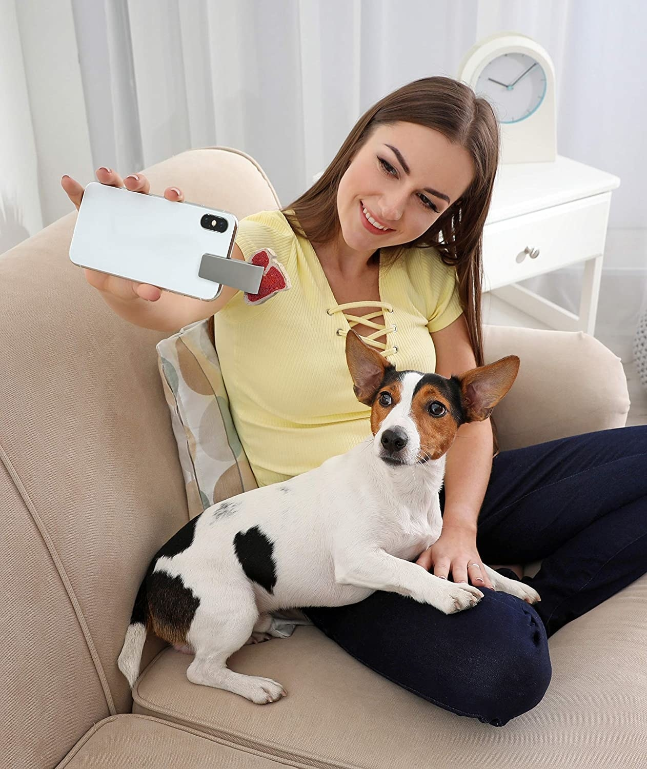 A person holds up their phone with the pet selfie tool while their puppy looks up at the camera