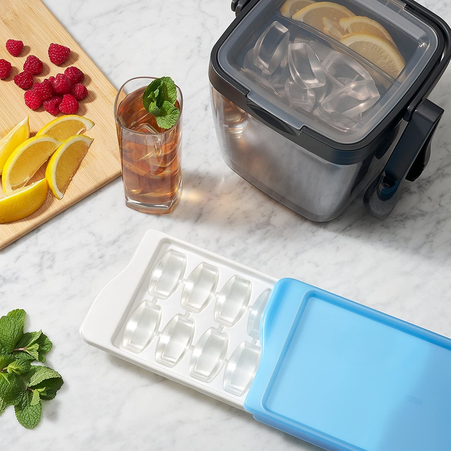 The lidded ice cube tray lays half open on a counter next to a glass of iced tea, a cutting board with fresh fruit, and some mint