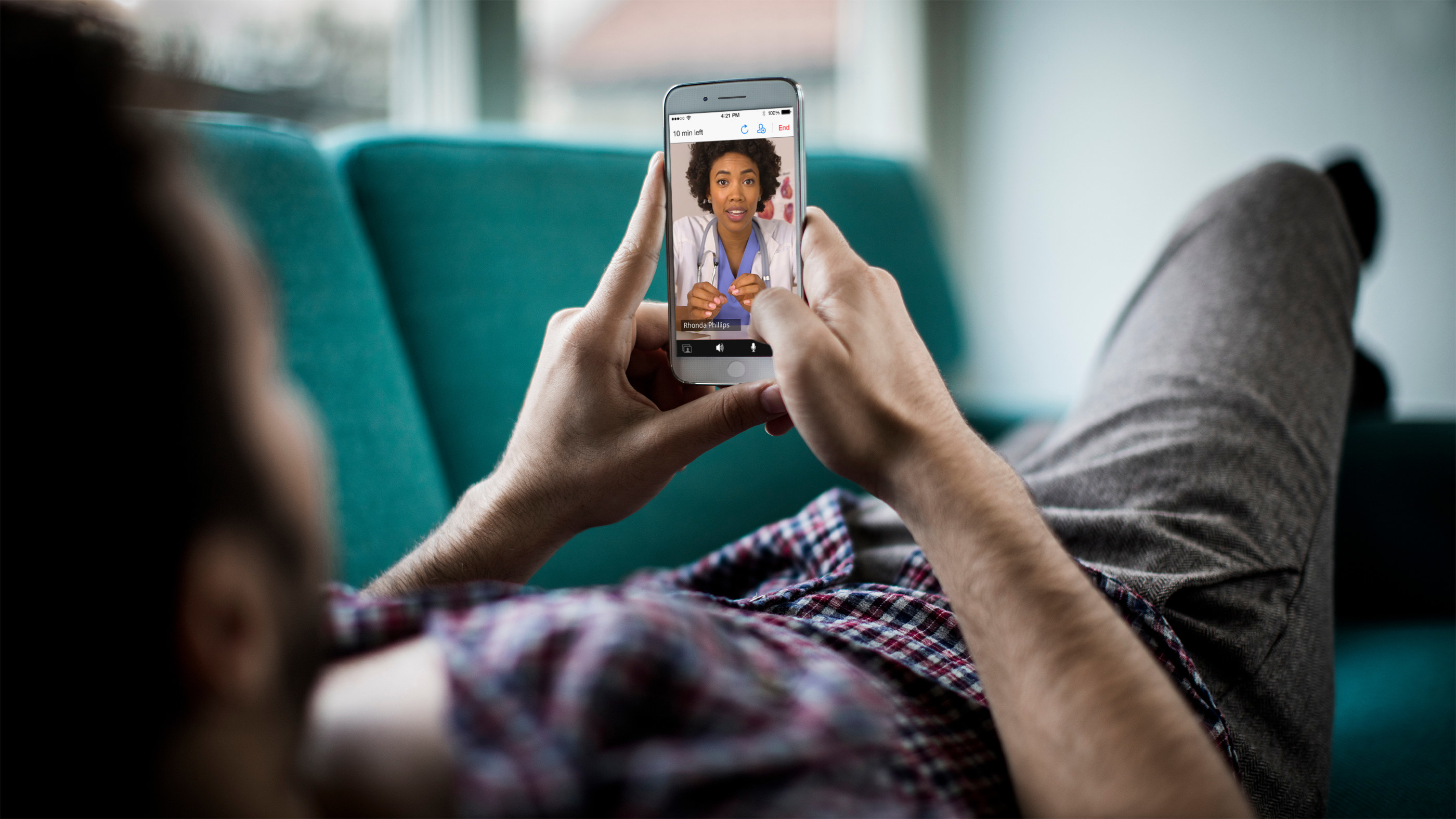 A woman lies on her couch and holds up her smartphone as she video conferences her therapist
