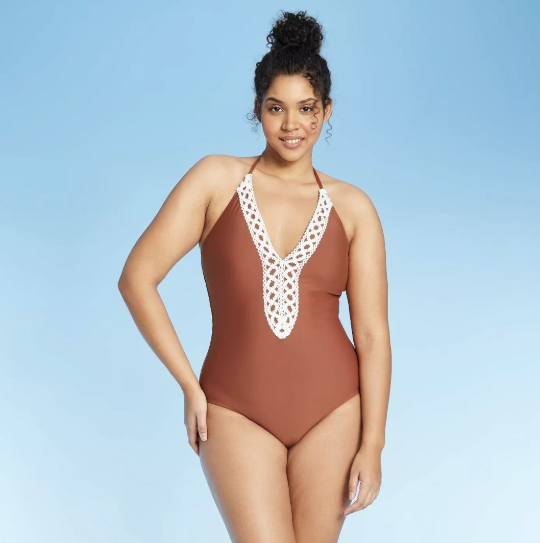 A model in a copper one piece with halter straps and white lace at the collar