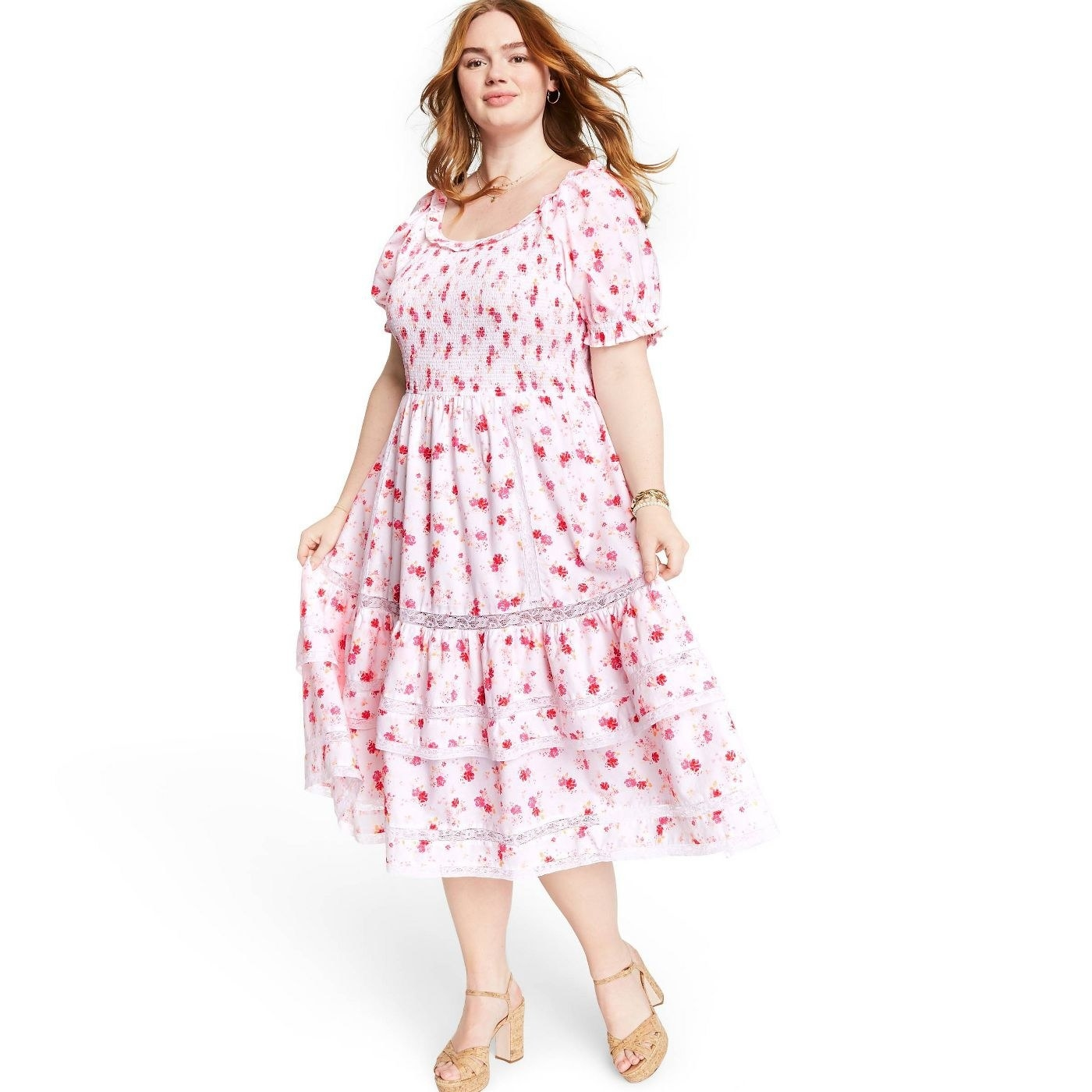A model in a tiered white midi dress with pink florals
