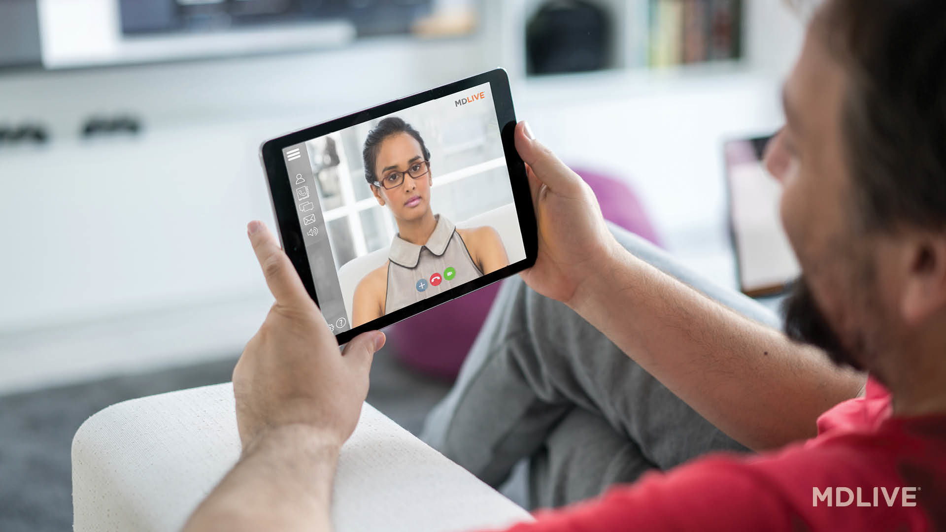 A person holds their tablet, video conferencing with their therapist from an arm chair