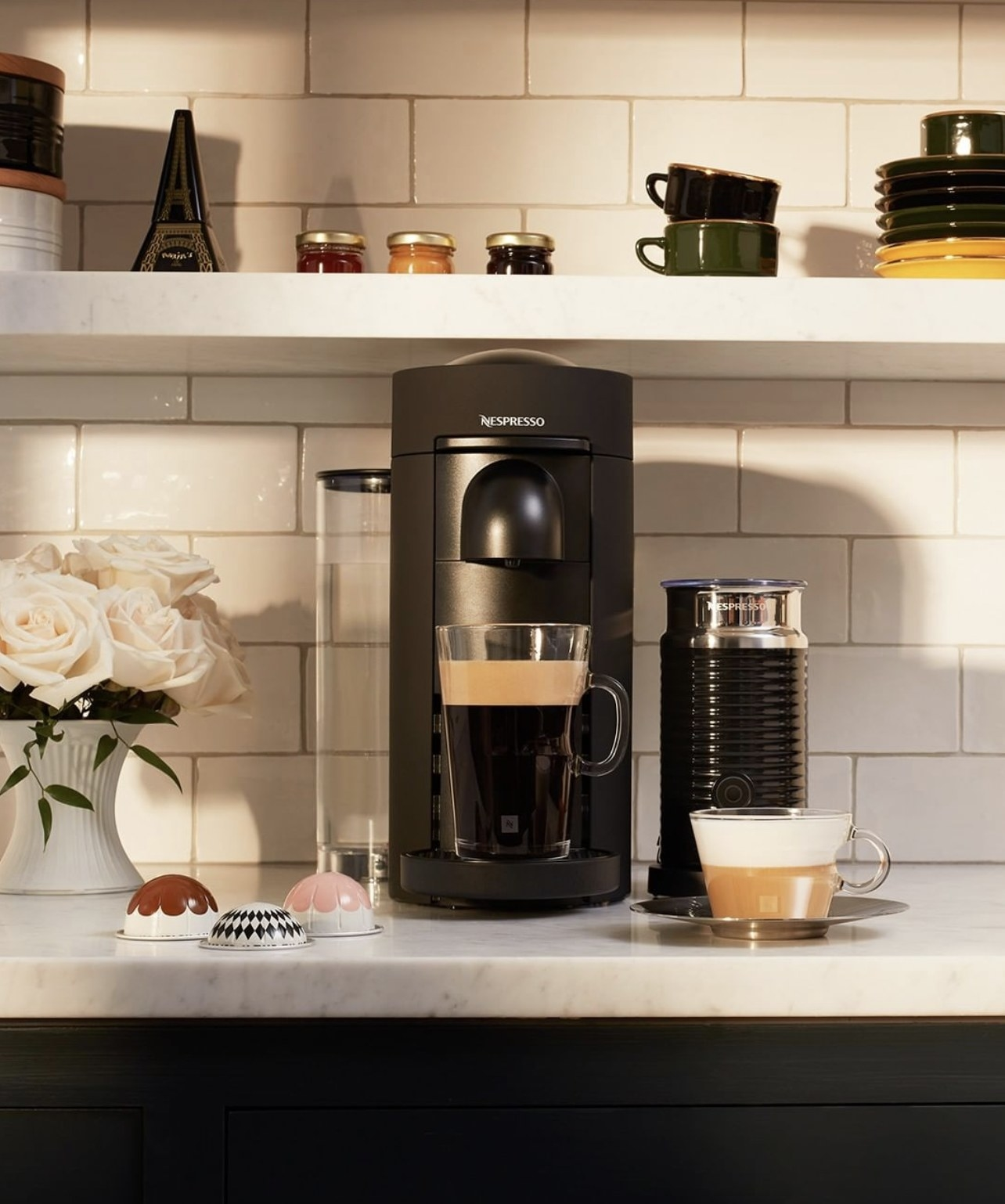 A black coffee maker with a glass full of coffee resting in its base