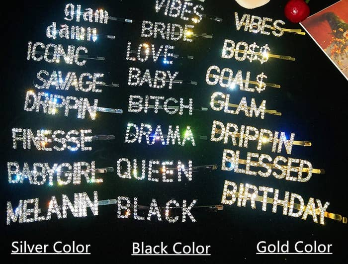 "Personalized rhinestone clips organized into group of black, silver, and gold. Clips read different words, such as, ""savage,"" ""melanin,"" and ""blessed"""