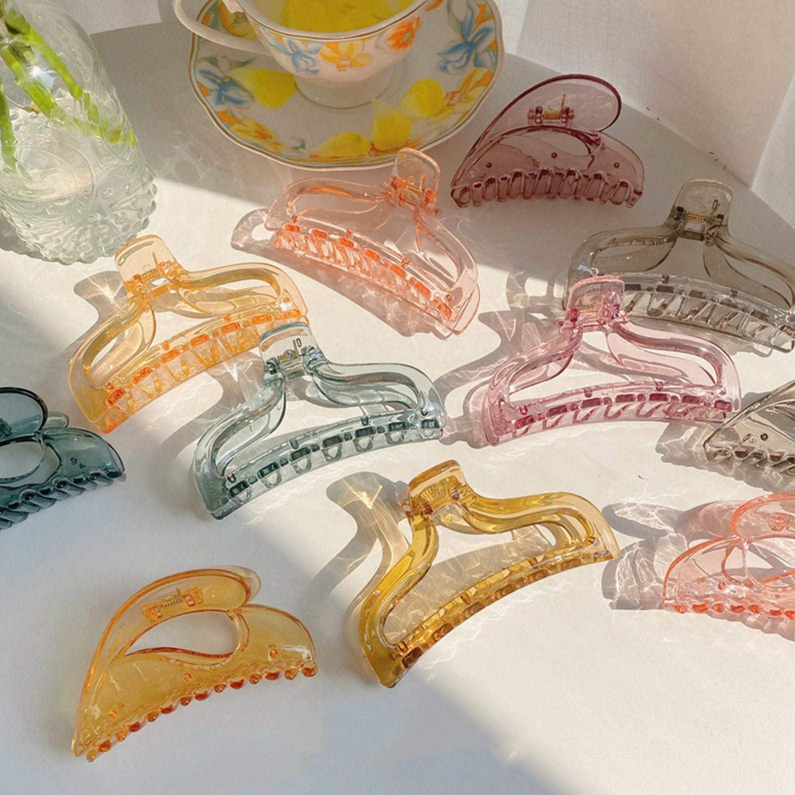 Numerous resin hair clips in different shapes and colors lay on a table. The resin is translucent and the clips are essentially thick frames as the middle is cut out