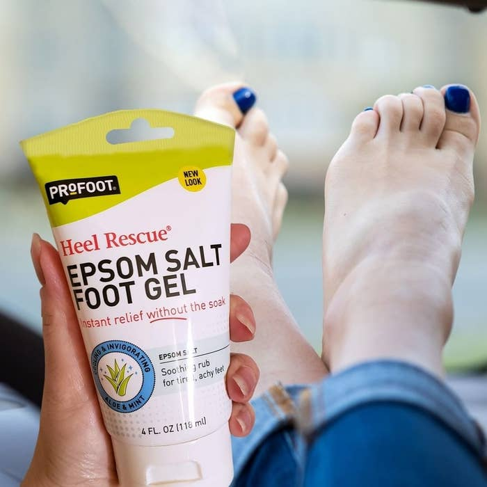 A person holding a tube of epsom salt foot gel in front of their feet