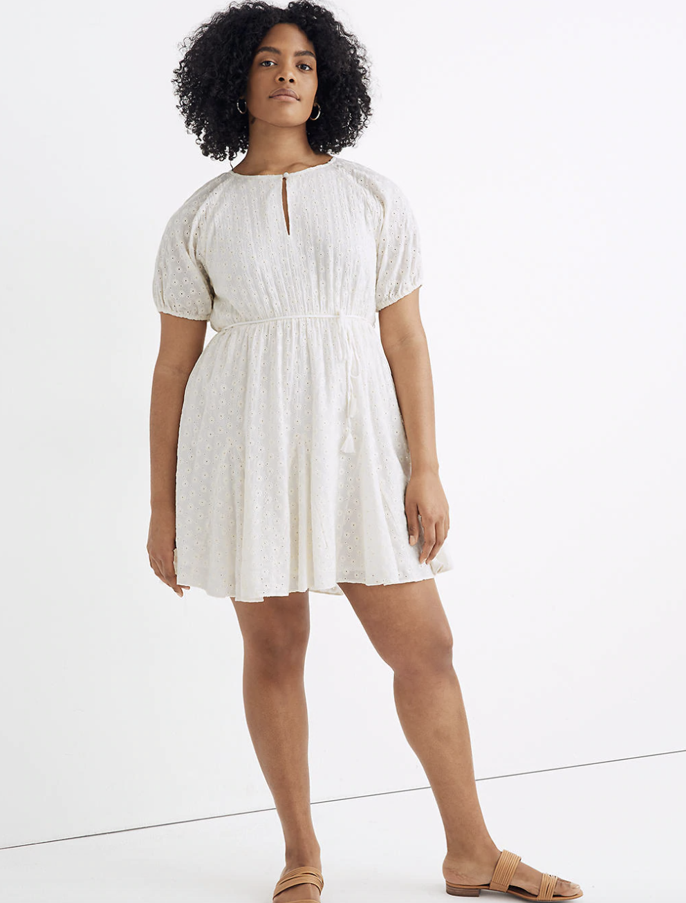 a model wearing a white short-sleeved eyelet dress with a thin rope belt, ends mid thigh