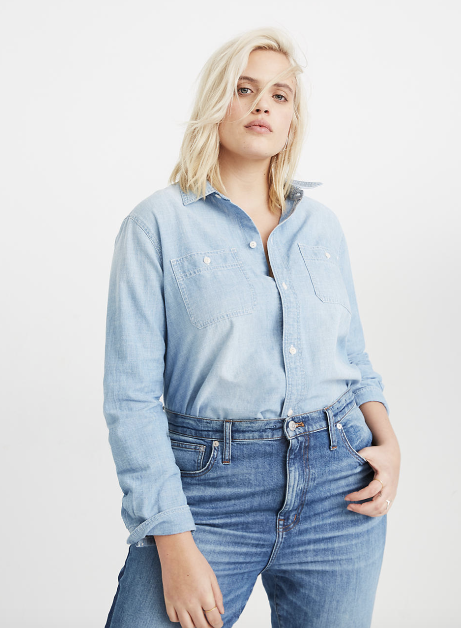 a model in medium blue jeans wearing a light wash longe sleeve chambray shirt with a collar and white buttons