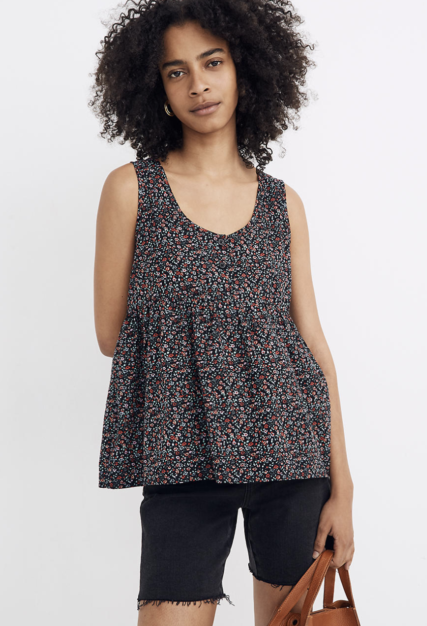 a model wearing a floral tank top with the black denim cut offs, they have a raw edge hem and end mid-thigh