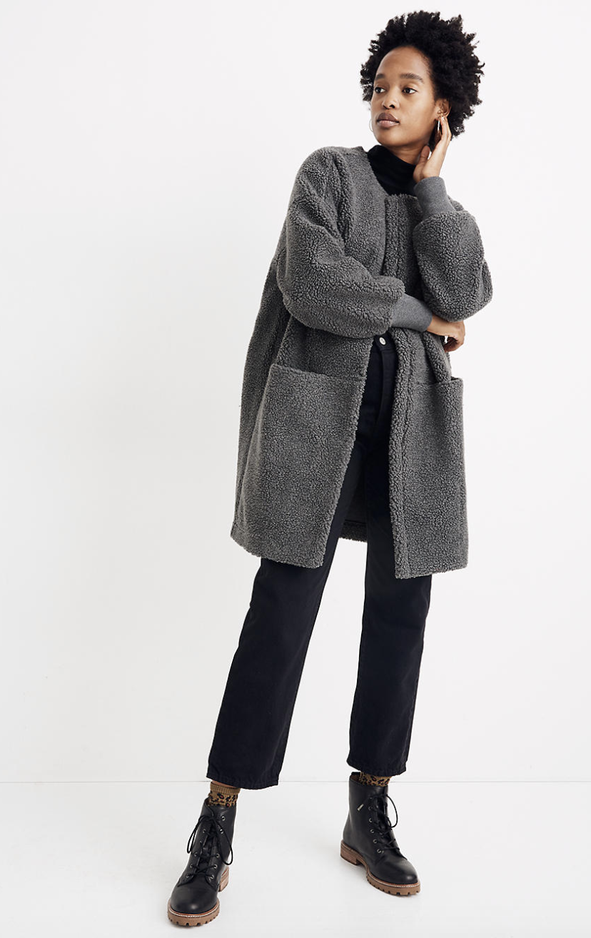 a model in a grey sherpa coat with two big pockets on either side and an open front