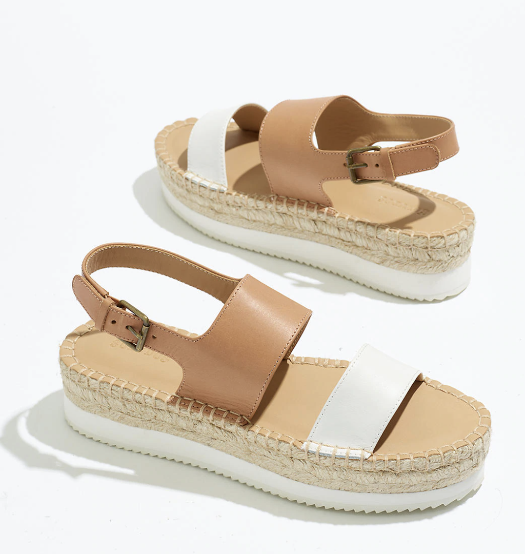 espadrille sandals with a white sole, tan bottom, a dark tan ankle strap, and white loop for the front of the foot