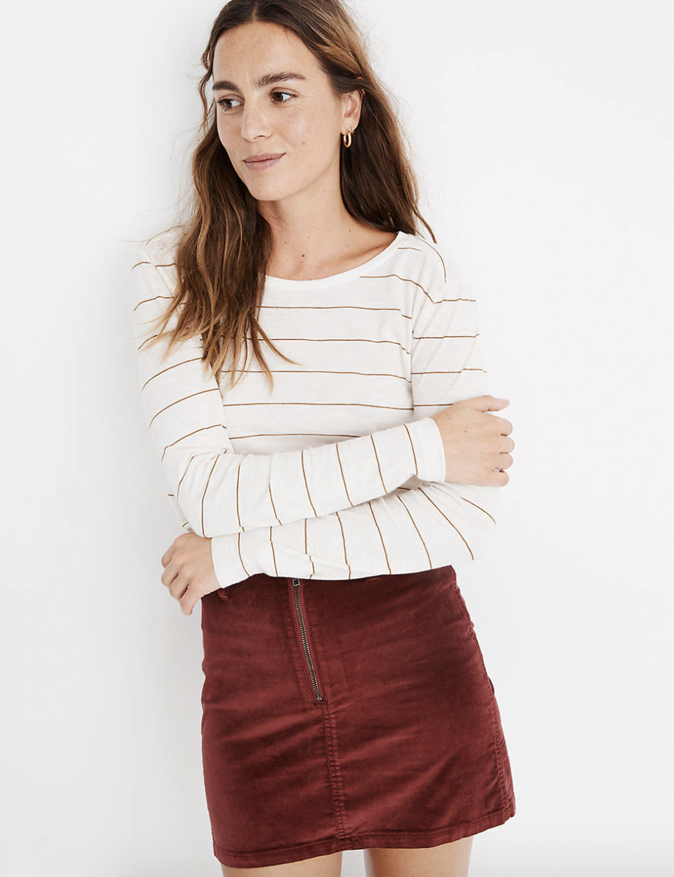 a model wearing the white long sleeve top that has thin burnt orange horizontal stripes throughout with a velvet burnt orange skirt