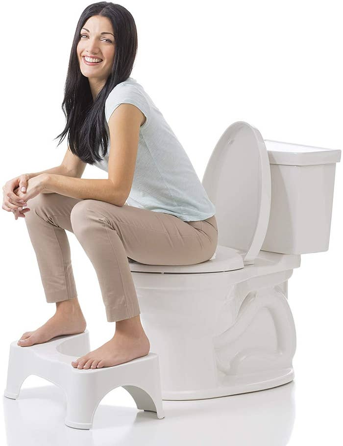 A person sitting on a toilet with a small stool under their feet