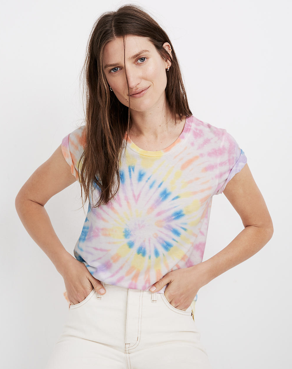 a model wearing the tie-dye tee which has a swirl of purple, pink, orange, yellow, and blue throughout it
