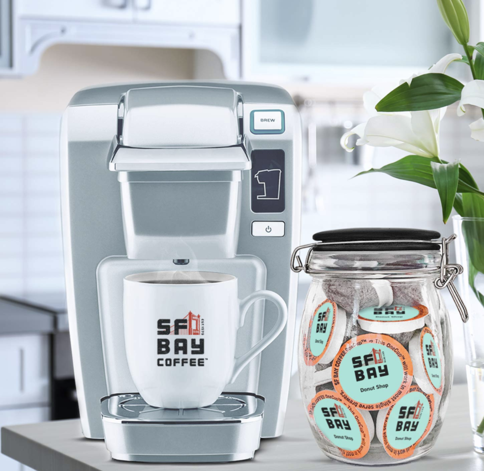 "Compostable coffee pods that say ""SF Bay Donut Shop"" next to a silver pod coffee machine."
