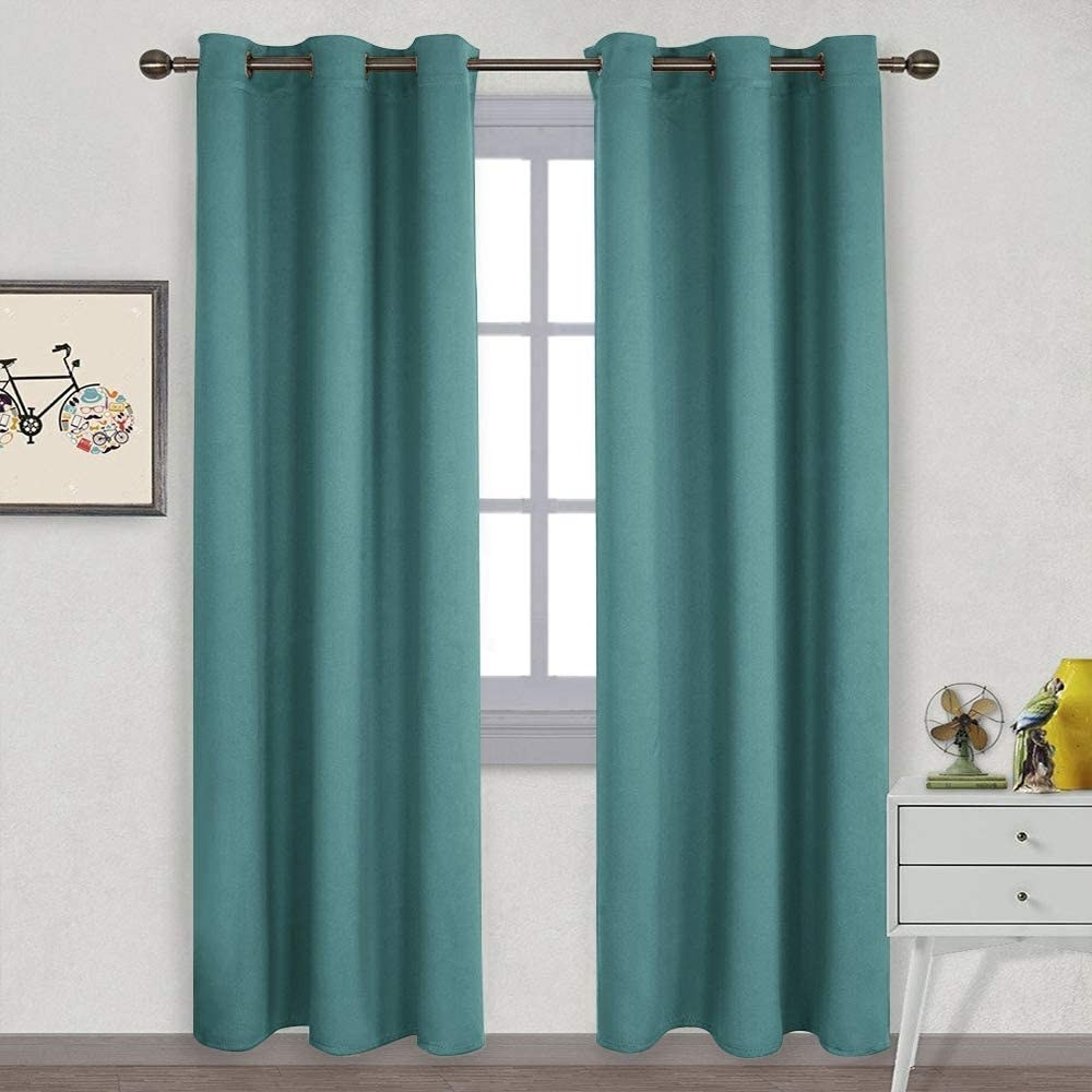 A set of teal blackout curtains hung up on a window