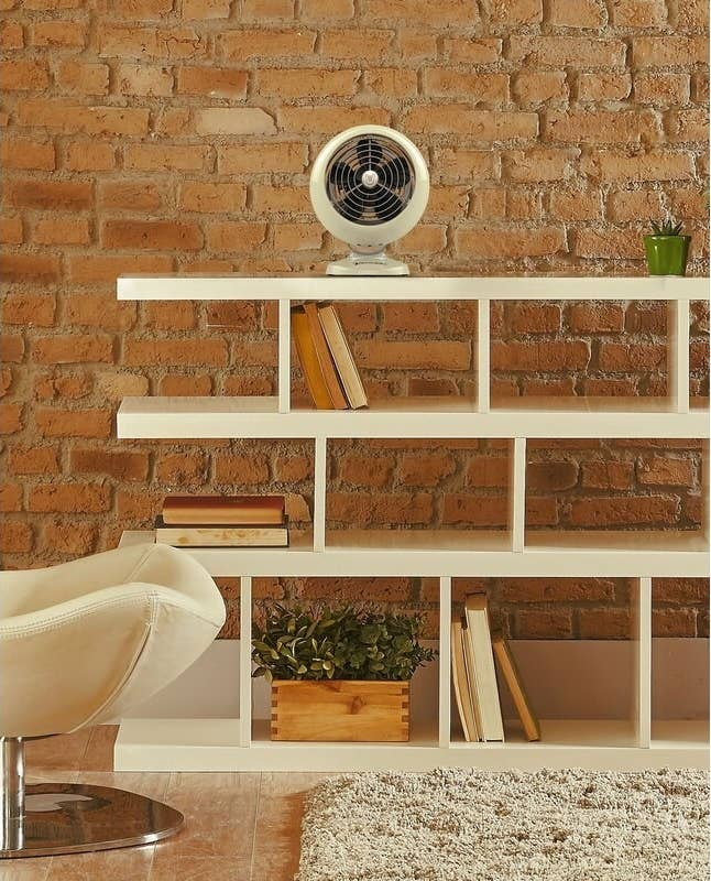 an off white, small, retro-looking fan sitting on top of shelving unit