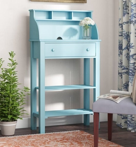 A vertical seafoam color desk with one drawer and three cubbies