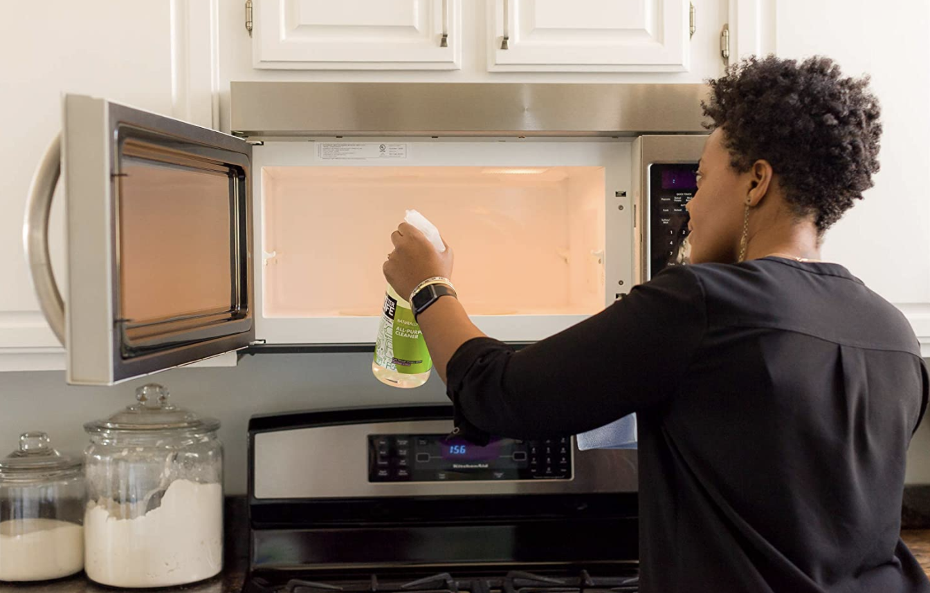 A model cleans their microwave with Better Life Natural All-Purpose Cleaner